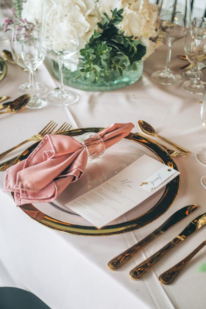 Złote podtalerze i sztućce, elegancka papeteria i różowe obrusy, czyli wesele w eleganckim stylu