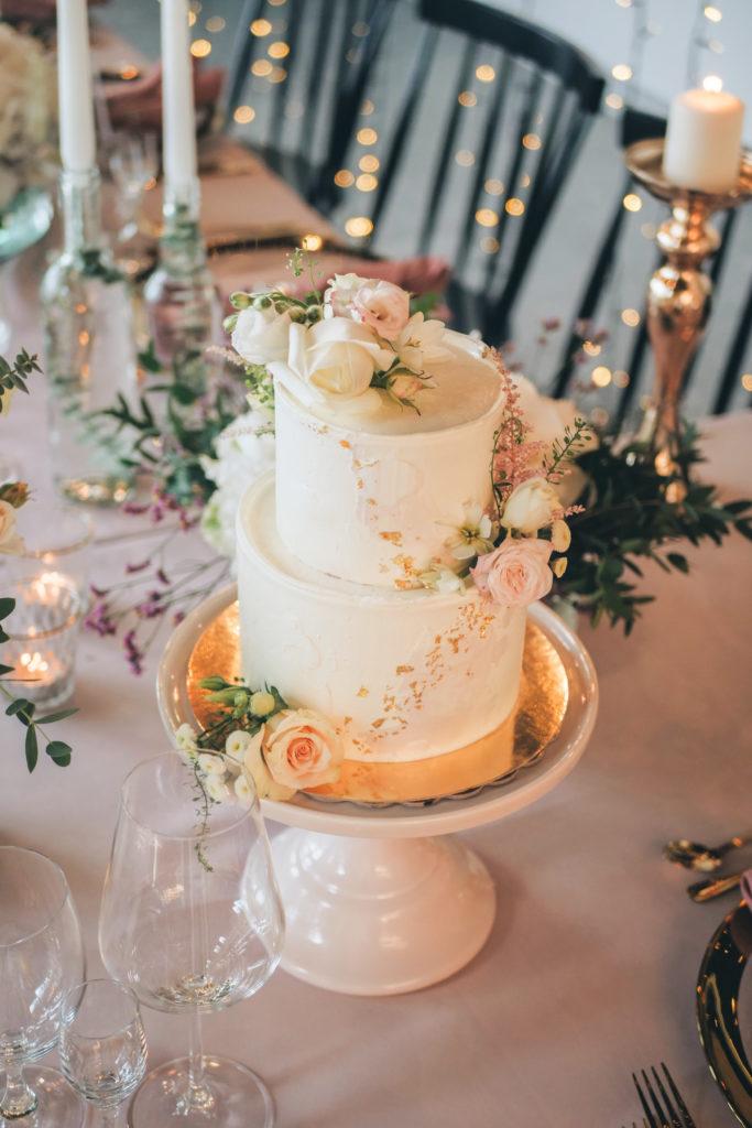 Tort ozdobiony kwiatami i płatkami złota na eleganckim weselu